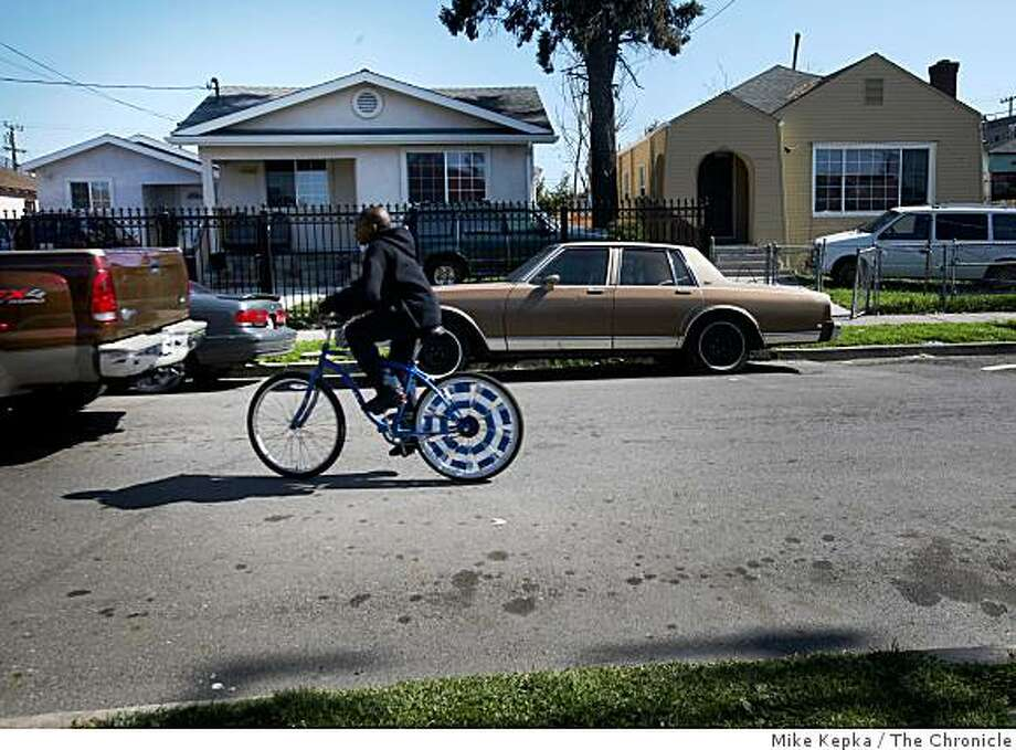 Days after a shooting incident that took the lives of 4 Oakland police officers, a boy rides his bike down 74th Avenue on Monday March 23, 2009 in Oakland, Calif. Photo: Mike Kepka, The Chronicle