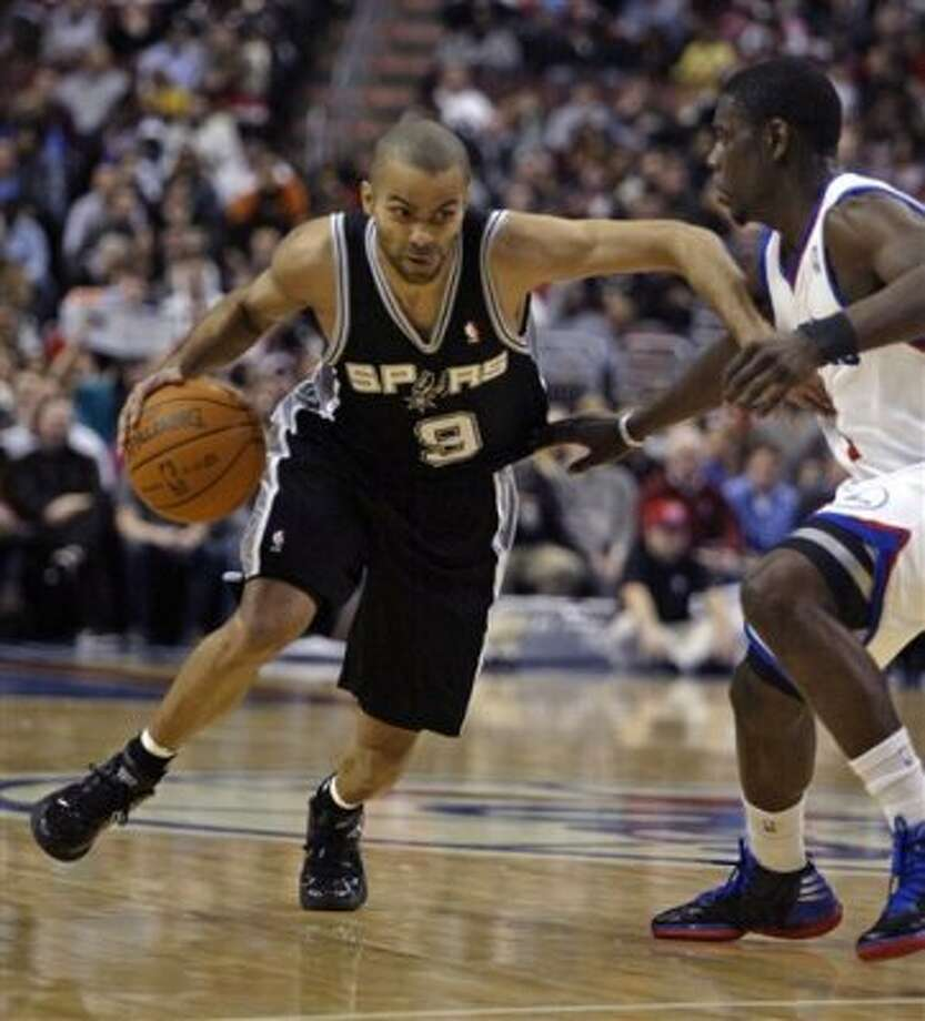 San Antonio Spurs' Tony Parker (9) drives against  Philadelphia 76ers' Jrue Holiday in the first half of an NBA basketball game on Wednesday, Feb., 8, 2012, in Philadelphia. (AP Photo/H. Rumph Jr ) (AP)