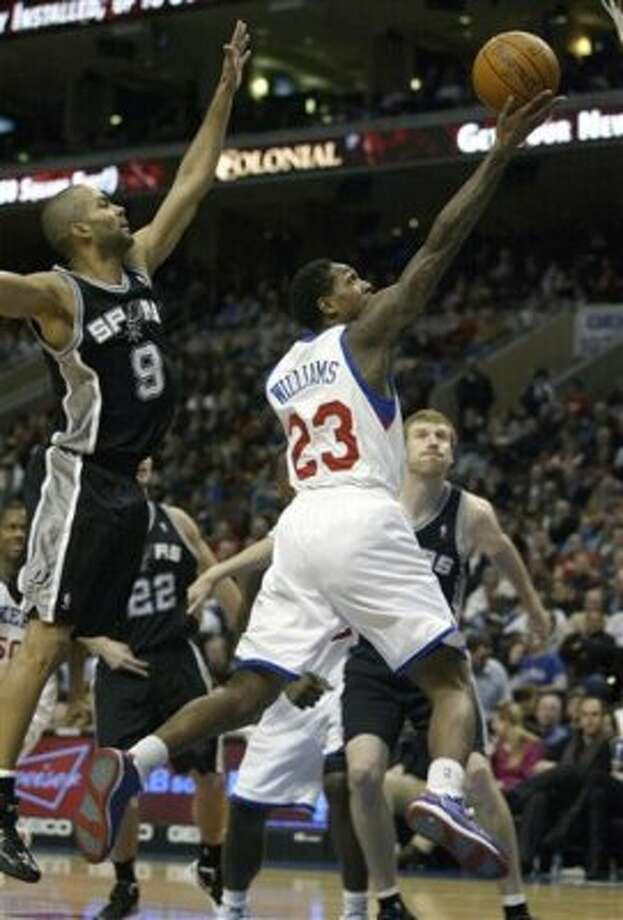 San Antonio Spurs' Tony Parker (9) defends as Philadelphia 76ers' Lou Williams (23) goes up for a shot in the second half of an  NBA basketball game on Wednesday, Feb., 8, 2012, in Philadelphia. The Spurs won 100-90. (AP Photo/H. Rumph Jr ) (AP)
