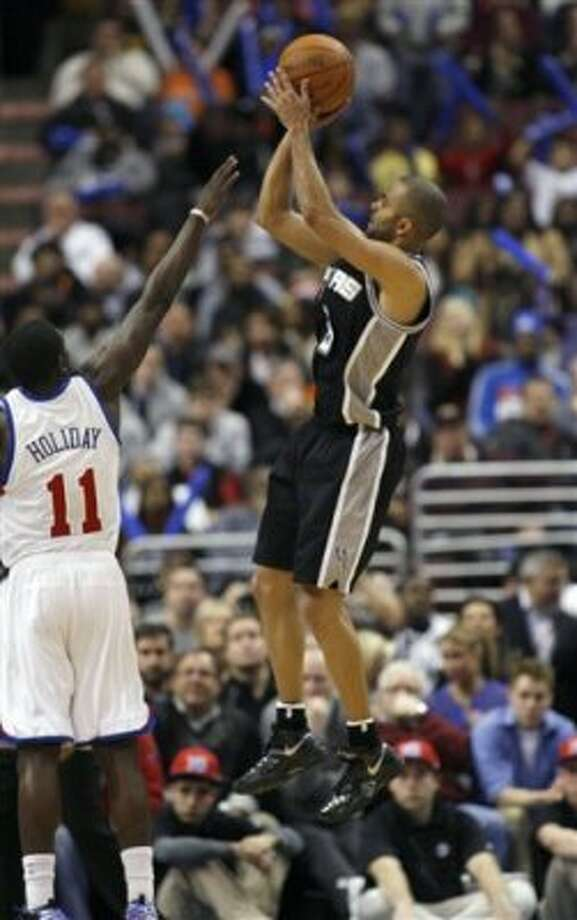 San Antonio Spurs' Tony Parker, right, goes up for shot as Philadelphia 76ers' Jrue Holiday (11) defends in the second half of an NBA basketball game on Wednesday, Feb., 8, 2012, in Philadelphia. The Spurs won 100-90. (AP Photo/H. Rumph Jr ) (AP)