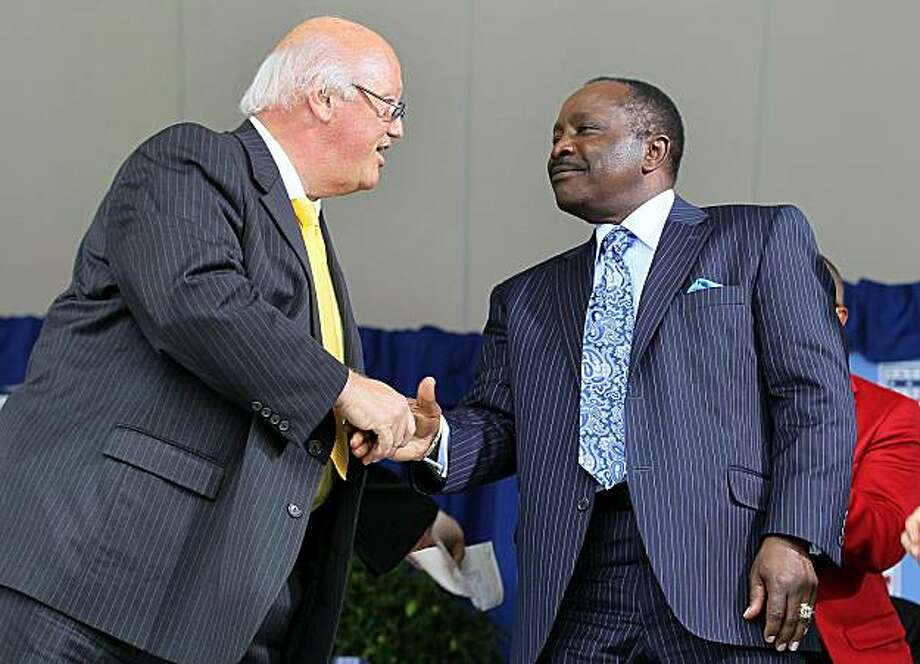 Jon Miller shakes hands with Hall of Famer Joe Morgan after Miller received the Ford C. Frick award for contributions in baseball broadcasting at Clark Sports Center during the Baseball Hall of Fame induction ceremony Sunday in Cooperstown, N.Y. Photo: Jim McIsaac, Getty Images