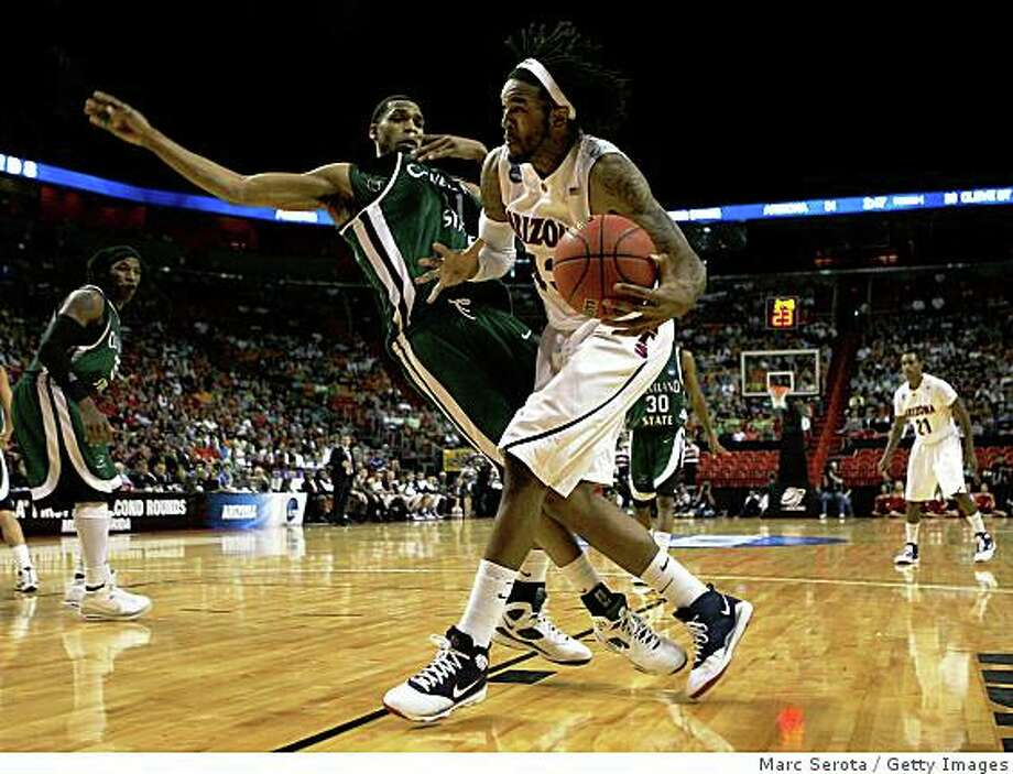 MIAMI - MARCH 22:  Forward Jordan Hill #43 of the University of Arizona Wildcats is defended by forward George Tandy #21 of  the Cleveland State University Vikings during the second round of the NCAA Division I Men's Basketball Tournament at the American Airlines Arena on March 22, 2009 in Miami, Florida.  (Photo by Marc Serota/Getty Images) Photo: Marc Serota, Getty Images
