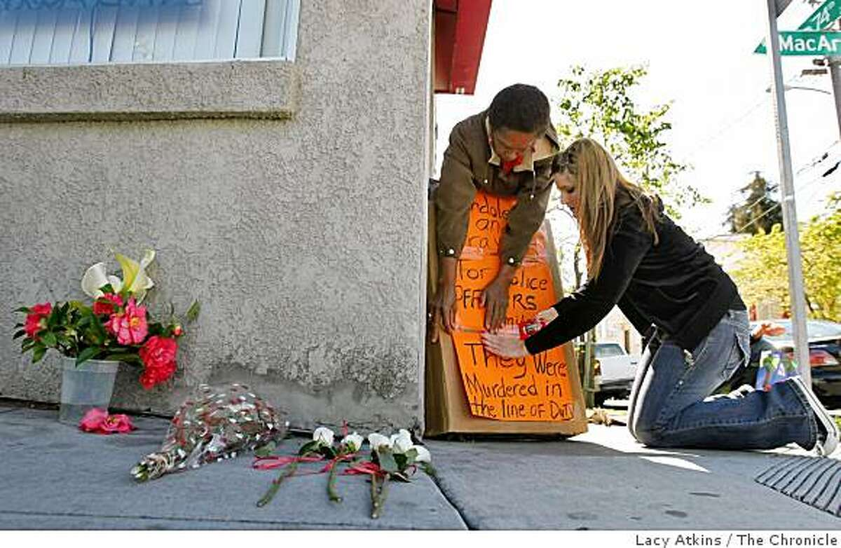 Rosalind Stone (left) and Kimberly Warne put up signs and flowers for the families of the four police officers who were killed Saturday in a shooting on the block of 74th Avenue and Hillside, Sunday March 22, 2009, in Oakland, Calif.