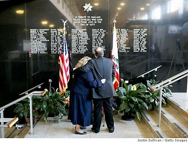 OAKLAND, CA - MARCH 22:  A couple embraces as they look at a memorial to Oakland police officers that have died in the line of duty in the lobby of the Oakland police department March 22, 2009 in Oakland, California. A fourth Oakland police officer has died a day after a shootout with a man following a traffic stop. The suspect was also shot and killed by police.  (Photo by Justin Sullivan/Getty Images) Photo: Justin Sullivan, Getty Images