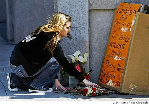 Kimberly Warne, whose roommate is a police officer, places flowers at a memorial for the families of the four police officers who were killed Saturday in a shooting on the block of 74th Avenue and Hillside, Sunday March 22, 2009, in Oakland, Calif. Photo: Lacy Atkins, The Chronicle