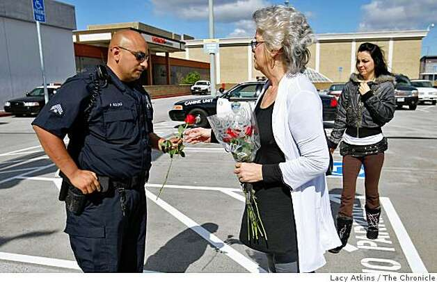 Oakland Police Officer F. Rojas (left) accepts a rose from Debbie Raess and daughter Shanna, outside the Eastmont Center Oakland Police substation, Sunday March 22, 2009, in Oakland, Calif. Raess wanted to thank the officers and tell them how sorry she was for the loss of their fellow officers. Photo: Lacy Atkins, The Chronicle