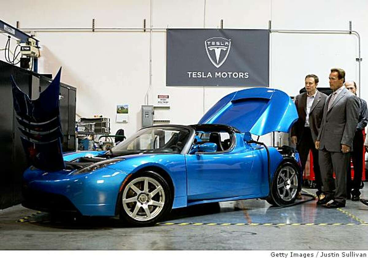 SAN CARLOS, CA - JUNE 30: California governor Arnold Schwarzenegger (R) and Tesla Motors Product Architect and Engineer Elon Musk look at a Tesla Roadster before a news conference June 30, 2008 at Tesla Motors in San Carlos, California. Governor Schwarzenegger announced that electric car company Tesla Motors will build a new manufacturing facility in California to manufacture its all-electric Tesla Roadster. The $109,000 2009 Tesla Roadster zero emissions vehicle is capable of traveling nearly 250 miles on a single charge and is capable of going 0-60 miles per hour in 3.9 seconds. (Photo by Justin Sullivan/Getty Images)