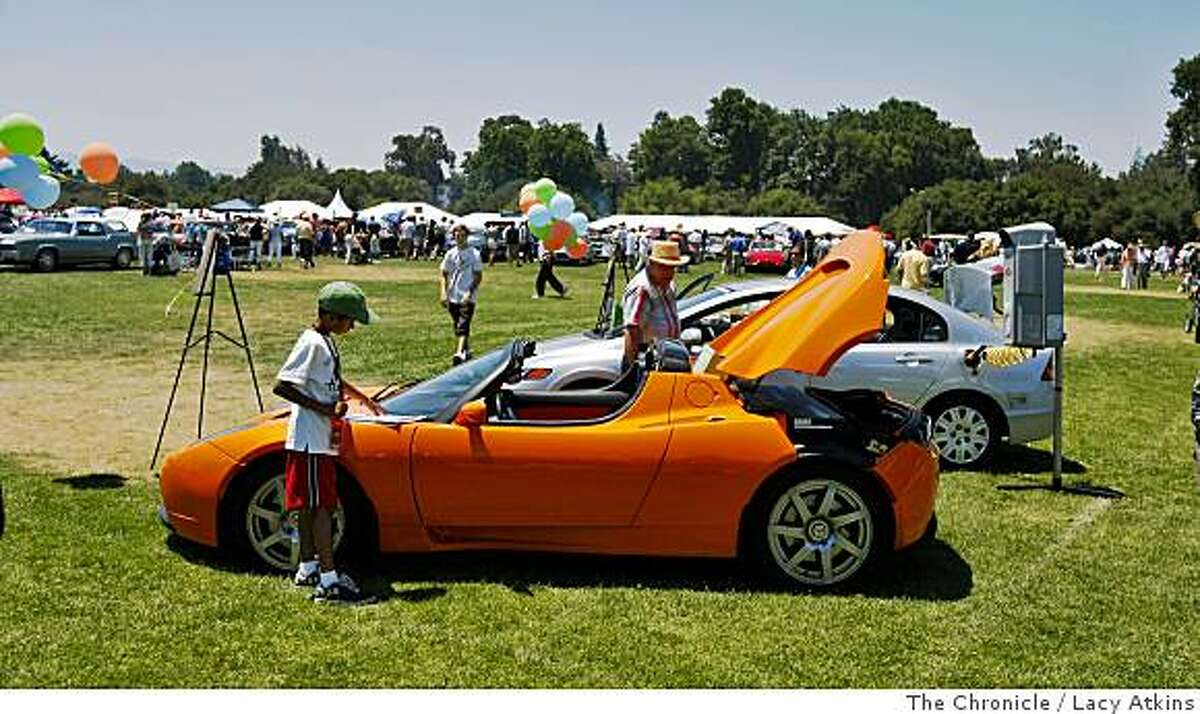 People of all ages look over the 2009 Tesla Roadster which is an eletric charged car on display at the Forty Second Palo Alto Concours d Elegance, Sunday June 22, 2008, in Palo Alto, Calif. Photo by Lacy Atkins /The Chronicle