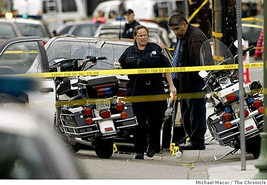 Police personnel pour over the first shooting scene where 2 of the 4 Oakland police officers were shot and all are in critical condition after a traffic stop on MacArthur Blvd. at 74th Ave., turned deadly  in Oakland, Calif. on Saturday March 21, 2009. Photo: Michael Macor, The Chronicle