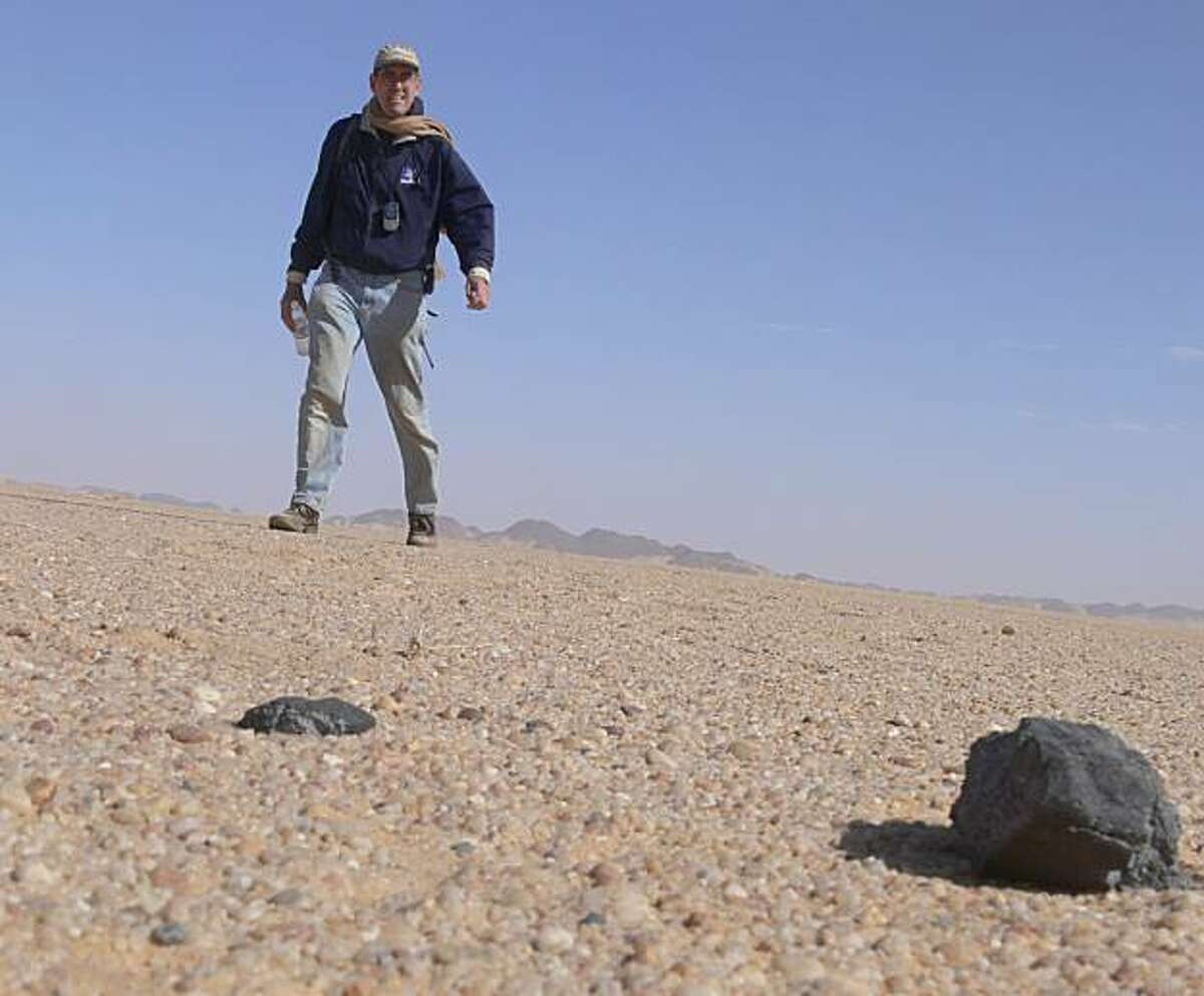 SETI Institute astronomer Peter Jenniskens in the Nubian desert with the first two meteorite fragments he found from the exploded asteroid.