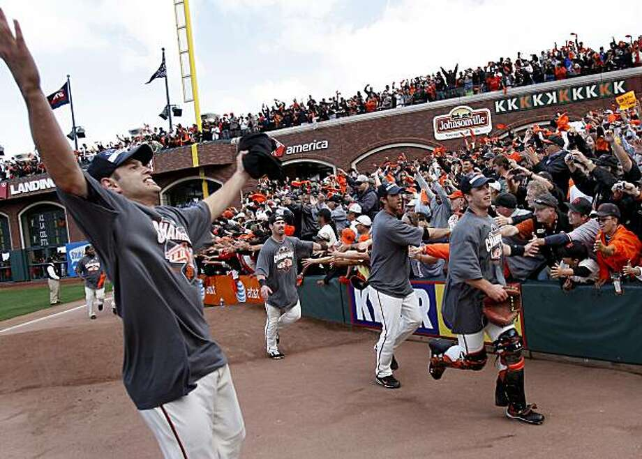 Freddy Sanchez (left) and the rest of the Giants, including Buster Posey (right), greet the crowd after beating the San Diego Padres to win the National League West championship Sunday. Photo: Brant Ward, The Chronicle