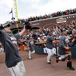 Freddy Sanchez (left) and the rest of the Giants, including Buster Posey (right), greet the crowd after beating the San Diego Padres to win the National League West championship Sunday.