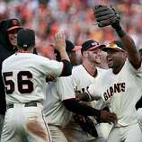 Giants players including Jonathan Sanchez (left) and Pablo Sandoval (right) celebrate on the pitcher's mound after beating the Padres on Sunday.