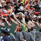 Giants fans stick out their hands for their league champions in centerfield after the game Sunday.