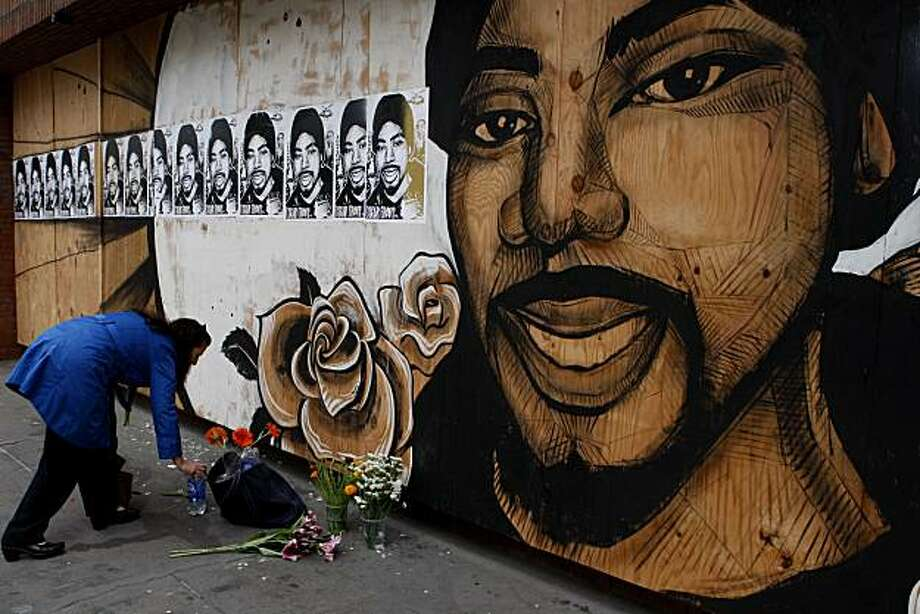 Oakland resident Julia Hutton lays flowers on the sidewalk in front of the Oscar Grant mural on 17th and Broadway on Friday following violent demonstrations over the Johannes Mehserle conviction on Thursday. Photo: John Sebastian Russo, The Chronicle
