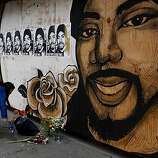 Oakland resident Julia Hutton lays flowers on the sidewalk in front of the Oscar Grant mural on 17th and Broadway on Friday following violent demonstrations over the Johannes Mehserle conviction on Thursday.