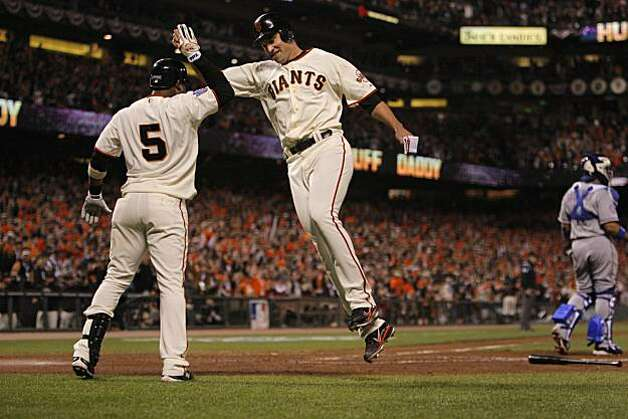 Giants Pat Burrell high-fives Juan Uribe after scoring on an Aubrey Huff single in the fifth inning as the San Francisco Giants take on the Texas Rangers in Game 1 of the World Series at AT&T Park in San Francisco, Calif., on Wednesday, October 27, 2010. Photo: Carlos Avila Gonzalez, San Francisco Chronicle