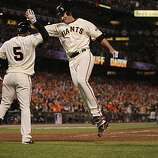 Giants Pat Burrell high-fives Juan Uribe after scoring on an Aubrey Huff single in the fifth inning as the San Francisco Giants take on the Texas Rangers in Game 1 of the World Series at AT&T Park in San Francisco, Calif., on Wednesday, October 27, 2010.