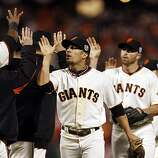 Giants high five after they win against the Rangers. The San Francisco Giants played the Texas Rangers at AT&T Park in San Francisco, Calif., in Game 1 of the World Series on Wednesday, October 27, 2010. The Giants defeated the Rangers 11-7