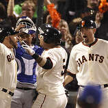 Giant's Cody Ross greets Juan Uribe (middle) in a 3 run homer during the fifth inning in Game One of the World Series with San Francisco Giants vs. Texas Rangers at AT&T park in San Francisco, Calif., on Monday, October 25, 2010.  Ranger's Benji Molina (background, left) and Giant's Aubrey Huff at right.