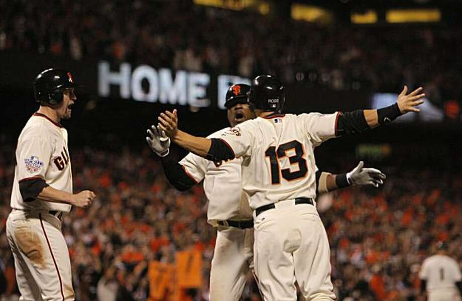 Giants Juan Uribe is greeted at the plate by Cody Ross and Aubrey Huff after hitting a 3-run home run in the fifth inning as the San Francisco Giants take on the Texas Rangers in Game 1 of the World Series at AT&T Park in San Francisco, Calif., on Wednesday, October 27, 2010. Photo: Carlos Avila Gonzalez, San Francisco Chronicle