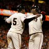 Juan Uribe (left) and Edgar Renteria greeted each other after scoring in the 8th inning on a hit by Aaron Rowand. The San Francisco Giants defeated the Texas Rangers 9-0 in game 2 of the 2010 World Series.