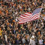 "An American flag is waved during ""God Bless America"" as the San Francisco Giants take on the Texas Rangers in Game 2 of the World Series at AT&T Park in San Francisco, Calif., on Thursday, October 28, 2010."