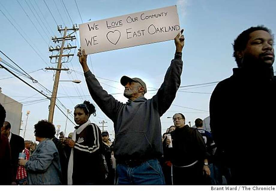 "Rudy Wilson of Oakland put his sentiments on a sign he held on MacArthur Blvd. during  a vigil Tuesday evening, March 24, for the four slain police officers. The sign reads: ""We love our community. We (heart) East Oakland."" Photo: Brant Ward, The Chronicle"