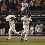 Giants Edgar Renteria gets a high five from third base coach Tim Flannery after hitting a solo home run in the fifth as the San Francisco Giants take on the Texas Rangers in Game 2 of the World Series at AT&T Park in San Francisco, Calif., on Thursday, October 28, 2010.