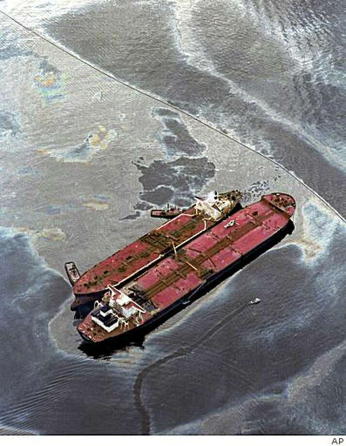 **FILE** The Exxon Baton Rouge, smaller ship, attempts to off load crude oil in a March 26,1989 file photo, from the Exxon Valdez after the Exxon Valdez ran aground in the Prince William sound, spilling more than 270,000 barrels of crude oil.  (AP Photo, File) Photo: AP