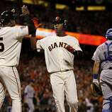 Juan Uribe (left) and Edgar Renteria scored on a hit by Aaron Rowand in the 8th inning. The San Francisco Giants defeated the Texas Rangers 9-0 in game 2 of the 2010 World Series.