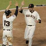 Giants Cody Ross, (left) and Aubrey Huff score on a Edgar Renteria single in the eighth inning to make it 6-0, as the San Francisco Giants take game 2, with a score of 9-0 over the Texas Rangers during the 2010 World Series on Thursday Oct. 28, 2010 in San Francisco, Calif.