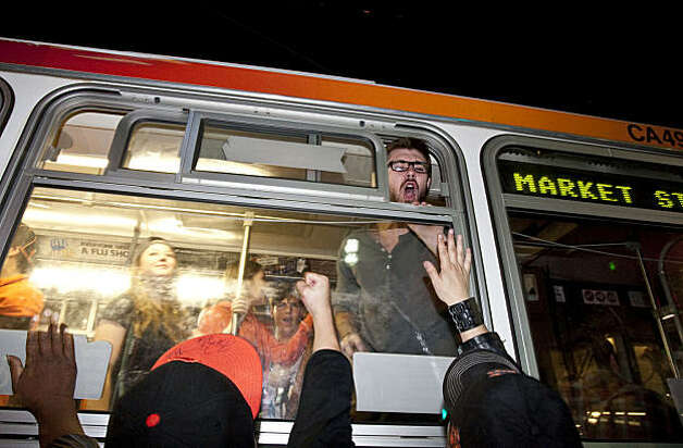 Giants fans crowd a bus in order to urge it's passengers to cheer while it  passes through the intersection of 4th and Townsend Streets in San Francisco, Calif., on Monday, November 1, 2010.  The Giants beat the Texas Rangers 3-1 in Game 5 of the World Series. Photo: Laura Morton, Special To The Chronicle