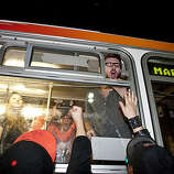 Giants fans crowd a bus in order to urge it's passengers to cheer while it  passes through the intersection of 4th and Townsend Streets in San Francisco, Calif., on Monday, November 1, 2010.  The Giants beat the Texas Rangers 3-1 in Game 5 of the World Series.
