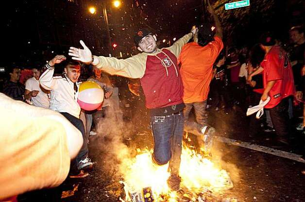 A Giants fan runs through a bonfire in celebration of the World Series win just after midnight at the intersection of 3rd Street and King Street in San Francisco, Calif., on Tuesday, November 2, 2010. Photo: Laura Morton, Special To The Chronicle