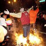 A Giants fan runs through a bonfire in celebration of the World Series win just after midnight at the intersection of 3rd Street and King Street in San Francisco, Calif., on Tuesday, November 2, 2010.