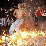A Giants fan celebrates the World Series win by running through a bonfire in the street at the intersection of 3rd Street and King Street in San Francisco, Calif., on Monday, November 1, 2010.