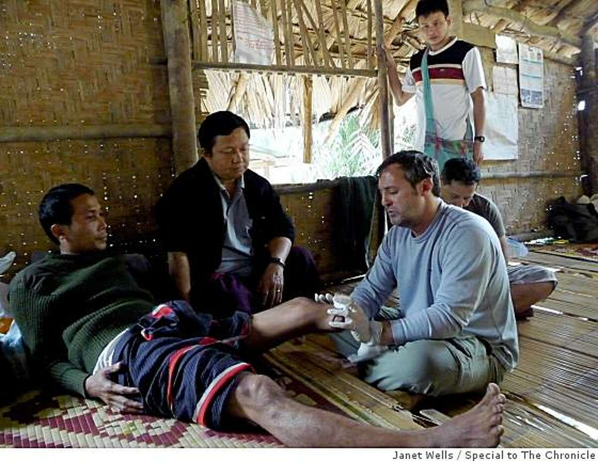 Dr. Larry Stock (right) conferring with a Karen villager who lost his leg in a landmine accident two years ago.