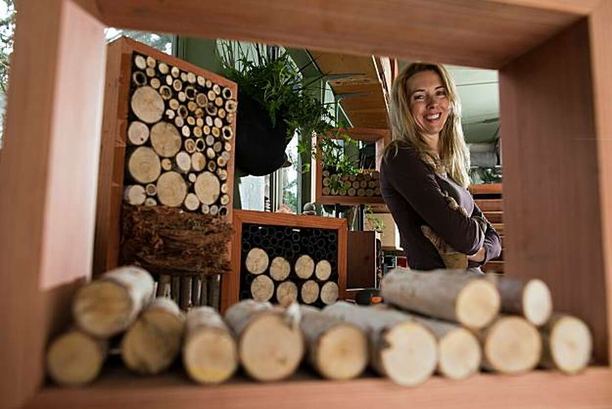 Colleen Smith, a woodsmith by trade, poses for a photograph with some of the bug houses she makes in her garage on October 21, 2010 in Pacifica, Calif. Photograph by David Paul Morris/Special to the Chronicle