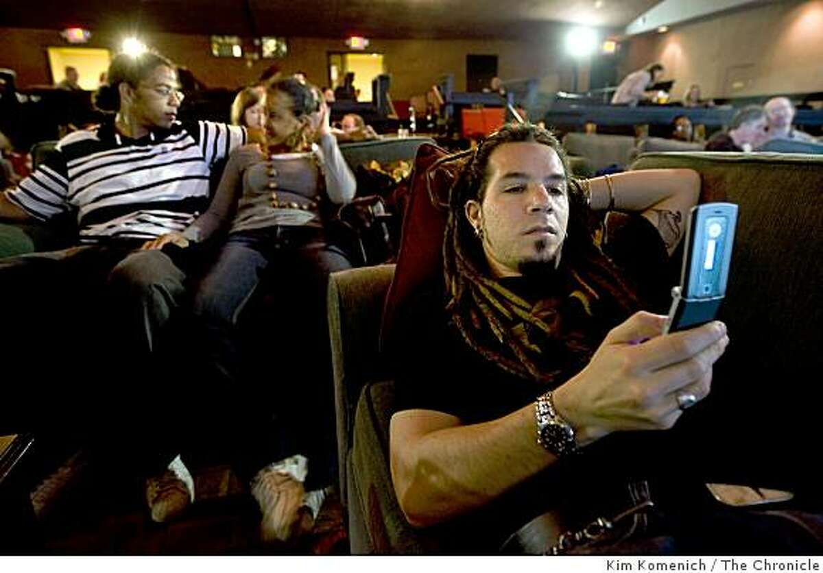 Seated in comfortable couches, Francisco Nanclares (R), texts a friend while Eric Wilkins of Walnut Creek, Calif., (L) and Maureen Akika of San Francisco, Calif., talk before the Parkway Speakeasy Theater in Oakland, Calif., shows
