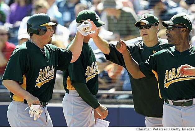 Landon Powell is congratulted by coaches Curt Young and Tye Waller after hitting a home run against the San Diego Padres during a spring training game at Peoria Stadium on March 7, 2009 in Peoria, Arizona. Photo: Christian Petersen, Getty Images