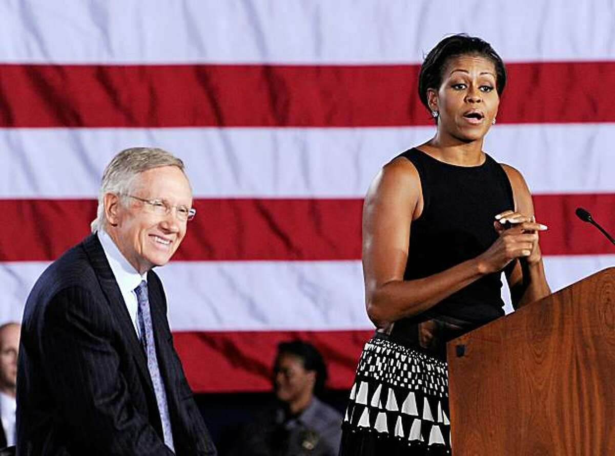NORTH LAS VEGAS, NV - NOVEMBER 01: U.S. Senate Majority Leader Harry Reid (D-NV) (L) looks on as first lady Michelle Obama speaks at a get-out-the-vote rally at Canyon Springs High School November 1, 2010 in North Las Vegas, Nevada. Recent polls show Reid, who is seeking his fifth term, four points behind Republican challenger Sharron Angle.