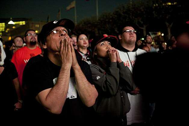 Giants fans Nicholas Renault of San Francisco, Anglea Short and Charlene Mendoza watch the Giants defeat the Texas Rangers to win the World Series in 5 games at the Civic Center Plaza on November 1, 2010 in San Francisco, Calif.  Photograph by David Paul Morris/Special to the Chronicle Photo: David Paul Morris, Special To The Chronicle