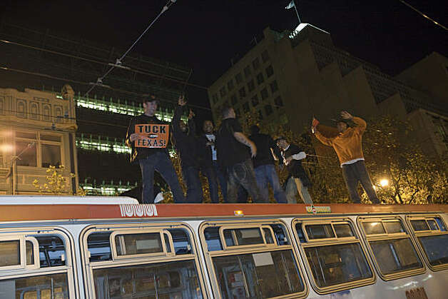 Giants fans celebrate on top of a Muni bus on Market Street after the Giants defeated the Texas Rangers to win the World Series in 5 games on November 1, 2010 in San Francisco, Calif.  Photograph by David Paul Morris/Special to the Chronicle Photo: David Paul Morris, Special To The Chronicle