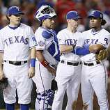 The Rangers wait on the pitcher's mound for relief pitcher Darren Oliver in the sixth inning of Game 4 of the World Series on Sunday.