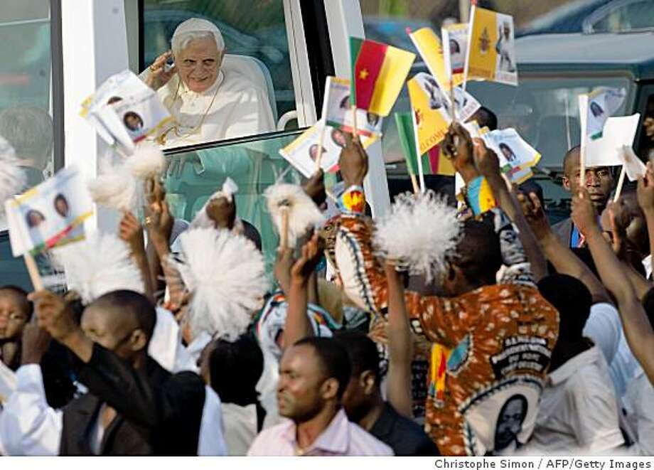 """Pope Benedict XVI waves to the crowd upon his arrival at Younde airport on March 17, 2009, on the first day of a six-day visit in Africa. Pope Benedict XVI brought the """"Christian message of hope"""" to Africa as he arrived in Cameroon today at the start of his first visit to the world's poorest continent as pontiff.    AFP PHOTO/ CHRISTOPHE SIMON (Photo credit should read CHRISTOPHE SIMON/AFP/Getty Images) Photo: Christophe Simon, AFP/Getty Images"""