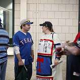 Kelly Martin (right) of Fort Worth, Texas, talks to her husband, Steve Martin, before Game 4 of the World Series at Rangers Ballpark on Sunday. Kelly Martin says it took nine hours to make the costume of a World Series ticket the day before.