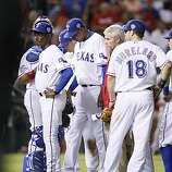 Texas Rangers relief pitcher Alexi Ogando comes out the game after injuring himself on a pitch in the sixth inning of Game 4 of the World Series on Sunday.