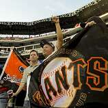Javier Valdez and Juan Huerta of Hayward wave a Giants banner as the Giants warm up before Game 4 of the World Series against the Texas Rangers on Sunday.