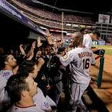 The Giants' Edgar Renteria gets high fives in the dugout after he scored a run off a double to center by Andres Torres in the seventh inning of Game 4 of the World Series on Sunday.
